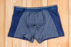 Голубые новые трусы хлопка для одежд мальчика на верхней части деревянных доск соперничают Стоковые Изображения RF