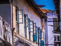 Голубые оконные рамы на желтой предпосылке стены глины стоковые изображения