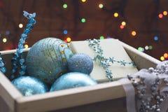 Голубые орнаменты Нового Года в деревянной коробке с fairy светами Стоковые Фотографии RF