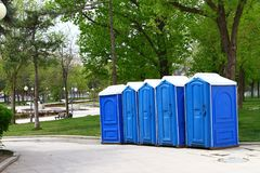 голубые передвижные туалеты одна дорога парка, деревья на предпосылке стоковые фото