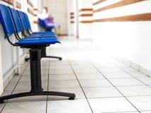 Голубые пустые пластичные места на конце коридора больницы вверх, pacient в blurried предпосылке стоковое изображение rf