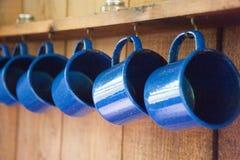 Голубые располагаясь лагерем кружки вися металл стоковое фото
