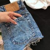Голубые шорты джинсовой ткани назад на деревянной предпосылке стоковая фотография