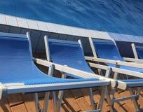 Голубые loungers выровнянные вверх на краю бассейна Стоковое Изображение