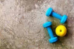 2 голубых веса, гантели и желтое яблоко на конкретной предпосылке Стоковые Изображения