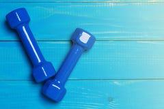 2 голубых гантели на голубых досках, концепции резвятся Стоковое Изображение