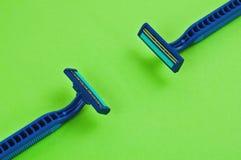 2 голубых пластичных устранимых бритвы с 2 лезвиями и влажностной прокладкой на пустой зеленой книге Стоковая Фотография