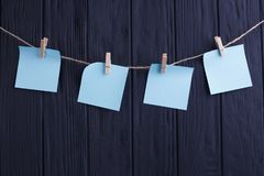 4 голубых пустых стикера на веревочке на черном деревянном backg планки Стоковое Изображение RF