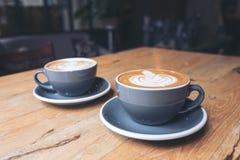 2 голубых чашки горячего кофе latte на винтажном деревянном столе в кафе Стоковая Фотография