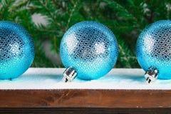 3 голубых шарика Нового Года лежат на деревянной коричневой полке окруженной ветвями ели Стоковое фото RF
