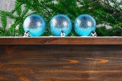 3 голубых шарика Нового Года лежат на деревянной коричневой полке окруженной ветвями ели Стоковая Фотография