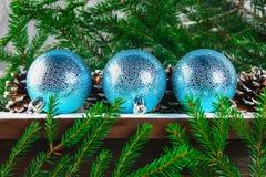 3 голубых шарика Нового Года лежат на деревянной коричневой полке окруженной ветвями ели Стоковое Фото