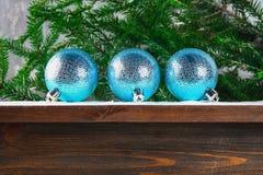 3 голубых шарика Нового Года лежат на деревянной коричневой полке окруженной ветвями ели Стоковые Фотографии RF