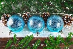 3 голубых шарика Нового Года лежат на деревянной коричневой полке окруженной ветвями ели Стоковое Изображение RF