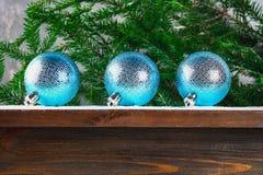 3 голубых шарика Нового Года лежат на деревянной коричневой полке окруженной ветвями ели Стоковое Изображение