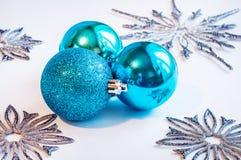 3 голубых шарика украшения на белой предпосылке с серебряными снежинками вокруг Стоковые Фото