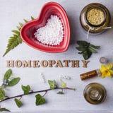 Гомеопатия, глобулы гомеопатии и бутылки Стоковые Фото