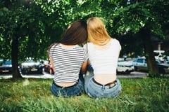 Гомосексуальные женщины обнимают и смеются над пока сидящ на траве стоковые изображения rf