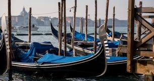 Гондолы на грандиозном канале в Венеции показывая иконические декоративные ferro/утюг на смычке шлюпок Стоковое Фото