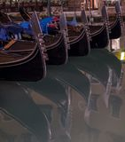 Гондолы припарковали на канале в Венеции, Италии показывая декоративные ferro/утюг на смычке шлюпок и risso стоковая фотография