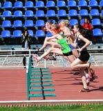 гонка в 100 метров барьеров девушок Стоковое Изображение