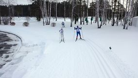 Гонка лыжи на следе в зиме footage Взгляд сверху состязаясь профессиональных лыжников в красочных костюмах ехать на следе стоковое изображение rf