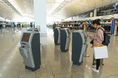 Гонконг, Китай - 19-ое марта 2018: Азиатская регистрация женщины путем использование машин регистрации киоска само- в стержне 1 н Стоковые Фотографии RF
