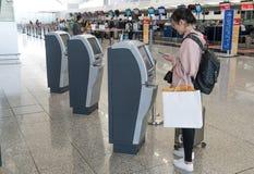 Гонконг, Китай - 19-ое марта 2018: Азиатская регистрация женщины путем использование машин регистрации киоска само- в стержне 1 н Стоковые Фото