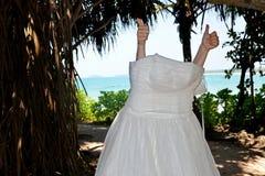 Гонорары невесты, руки с жестом классифицируют Невеста кладет дальше платье, свадьбу и медовый месяц в тропики на остров o стоковая фотография
