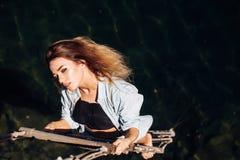 Гонор ее единственный стимул Чувственный вид женщины на веревочке над поверхностью воды Сексуальная женщина взбираясь вверх лестн стоковые изображения