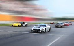 Гоночные автомобили участвуют в гонке на трассе на высокой скорости стоковые изображения