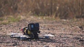гоночный дрон фпч взлетает с поверхности земли, поднимая пыль и камни видеоматериал
