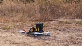 гоночный дрон фпч взлетает с поверхности земли, поднимая пыль и камни сток-видео