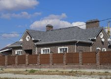 Гонт асфальта Декоративные гонт битума на крыше дома кирпича Загородка сделанная из рифлёного металла стоковое фото