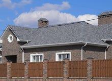 Гонт асфальта Декоративные гонт битума на крыше дома кирпича Загородка сделанная из рифлёного металла стоковые изображения rf