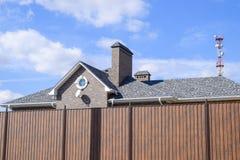 Гонт асфальта Декоративные гонт битума на крыше дома кирпича Загородка сделанная из рифлёного металла стоковая фотография