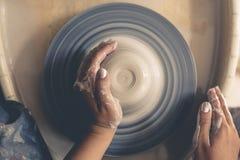 Гончар женщины вручает работу на колесе гончарни, взгляд сверху стоковая фотография