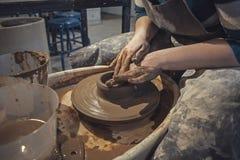 Гончар женщины мастера в рисберме на работе Художник мастера формирует кувшин с его руками на колесе гончарни стоковое изображение