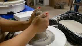 Гончар формирует продукт глины на колесе гончара видеоматериал