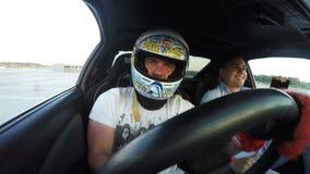 Гонщик крупного плана управляет автомобилем спорт и Гай делает Selfie видеоматериал