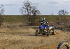 Гонщик Мотовездехода принимает поворот во время гонки на пылевоздушной местности Стоковые Изображения