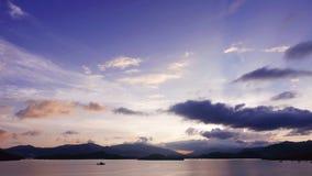 Гора, небо cloudscape, шлюпка на море на заходе солнца Стоковая Фотография