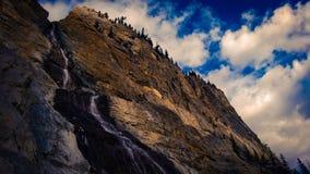Гора свертывая над водой горы солнечного света и каскада облаков падает Стоковые Изображения RF