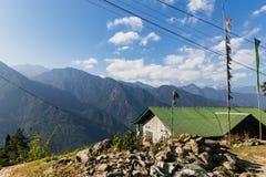 Гора Kangchenjunga с облаками выше и зеленым домом крыши Среди зеленых холмов которые осматривают в вечере в северном Сиккиме, Ин Стоковое Изображение