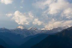 Гора Kangchenjunga с облаками выше Среди зеленых холмов и деревьев которые осматривают в вечере в северном Сиккиме, Индии Стоковое Изображение