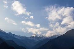 Гора Kangchenjunga с облаками выше Среди зеленых холмов и деревьев которые осматривают в вечере в северном Сиккиме, Индии Стоковое фото RF