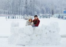Горизонтальная деревни зимы стены снега любящих пар смешная говоря смеясь над счастливая красивая Стоковые Изображения RF