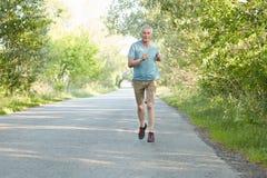 Горизонтальная съемка активного старшего мужчины бежит на асфальте очень быстро, одетый в spotswear, идет внутри для спорта регул стоковая фотография