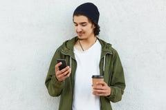 Горизонтальная съемка довольного сконцентрированного человека носит стильный headgear, носит на вынос кофе, сети surfes социальны стоковое изображение rf