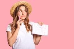 Горизонтальная съемка приятной смотря женщины с внимательным выражением, носит headgear и случайная футболка, держит календарь с стоковое изображение